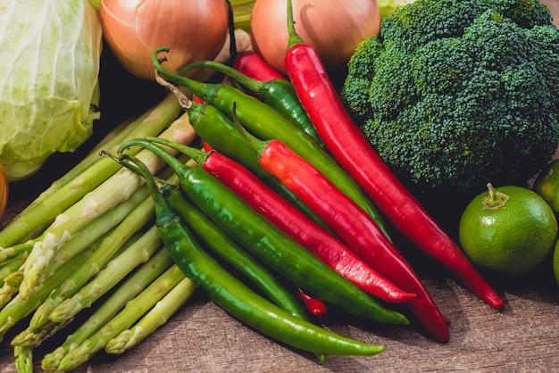 Roter und grüner paprika und verschiedene arten des gemüses als hintergrund auf holztisch Premium Fotos