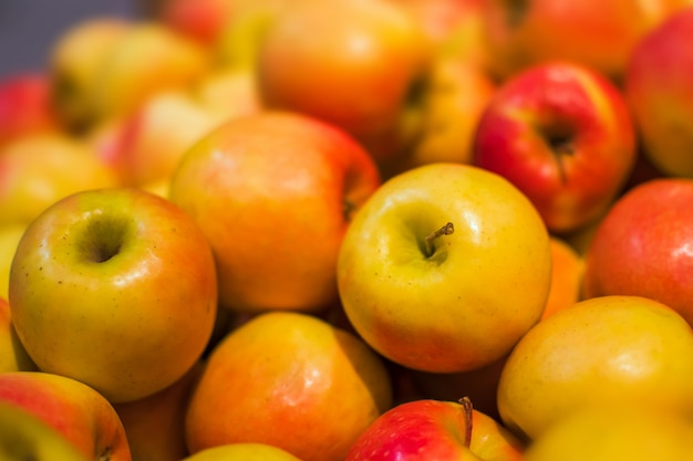 Roter und orange apfelhintergrund voll von orangen. frischer roter apfel auf dem markt. Premium Fotos