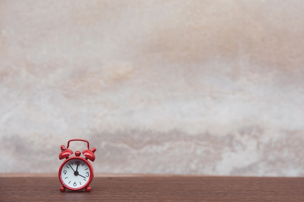 Roter wecker auf hölzernem hintergrund der dunklen planke der tabelle mit kopienraum Premium Fotos