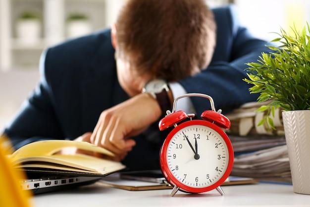 Roter wecker zeigt nahaufnahme der späten zeit und männlichen sekretär des müden büros in der klage halten auf dem tabellenarbeitsplatz voll von prüfungspapieren ein schläfchen. Premium Fotos