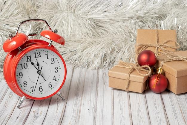 Roter weinlesewecker und drei geschenkboxen auf einem holztisch verziert mit einer girlande und roten weihnachtsbällen für das neue jahr oder das weihnachten. kopieren sie platz Premium Fotos
