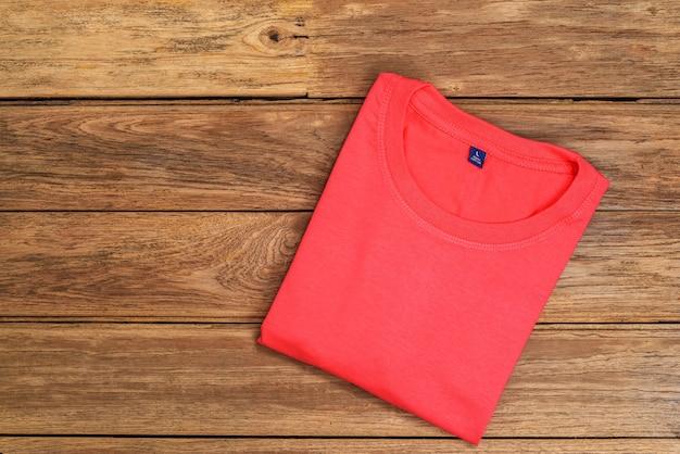 Rotes baumwoll-t-shirt auf hölzernem hintergrund. Premium Fotos
