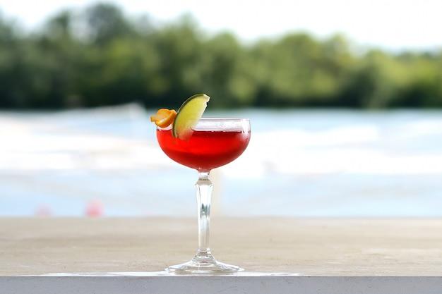 Rotes cocktail in einem becherglas mit einer limettenscheibe. mit blumendekor Premium Fotos