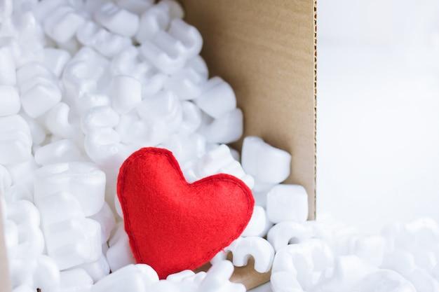 Rotes filzherz in verpackungsbox mit vielen weißen styroporpellets Premium Fotos