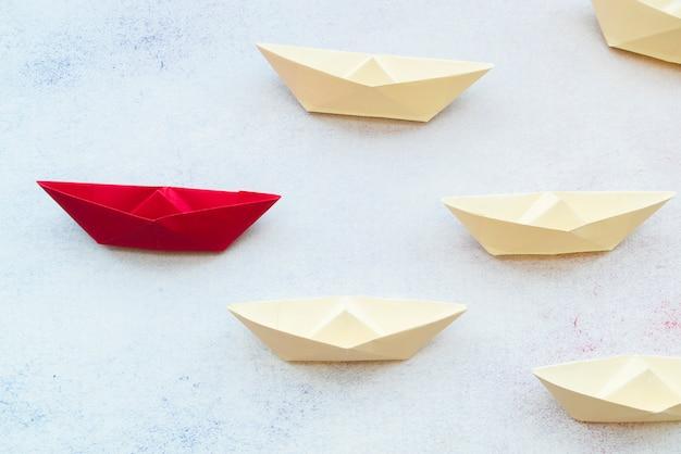 Rotes führerpapierschiff, das unter weiß auf strukturiertem hintergrund führt Kostenlose Fotos