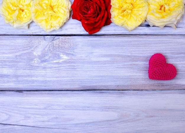 Rotes gestricktes herz auf einem weißen hölzernen hintergrund Premium Fotos