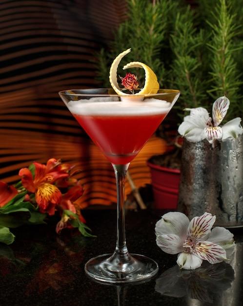 Rotes getränk in martini-glas mit zitronenschale in einer schwach beleuchteten bar mit blumen garnieren Kostenlose Fotos