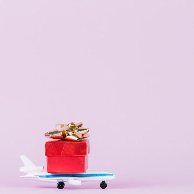 Rotes giftbox mit goldenem bogen über dem spielzeugflugzeug gegen rosa hintergrund Kostenlose Fotos
