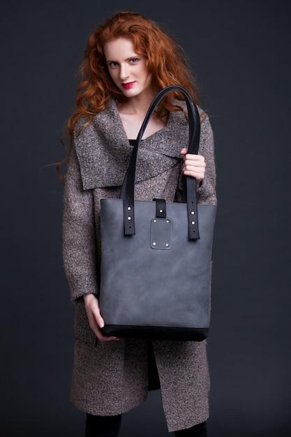 Rotes haarmode-modell, das große dunkelblaue ledertasche auf dunklem hintergrund hält. mädchen mit langem pullover. Premium Fotos