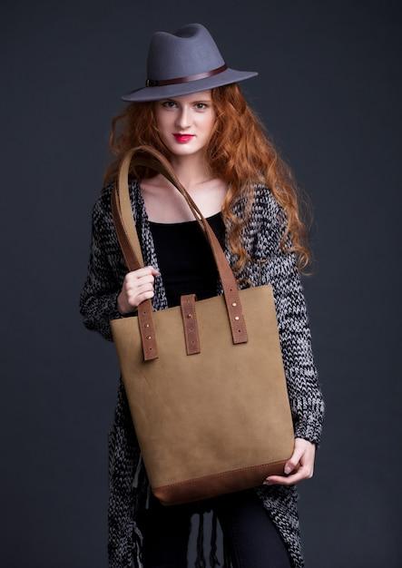 Rotes haarmode-modell, das große ledertasche auf dunklem hintergrund hält. mädchen mit pullover und hut. Premium Fotos