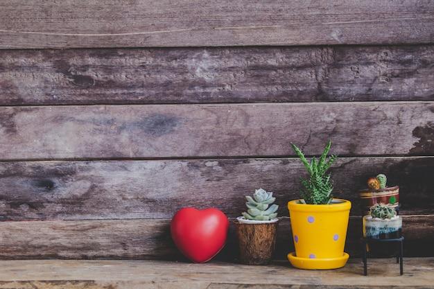 Rotes herz des valentinsgrußes verziert mit kaktuspotentiometern auf hölzernem rustikalem hintergrund Premium Fotos
