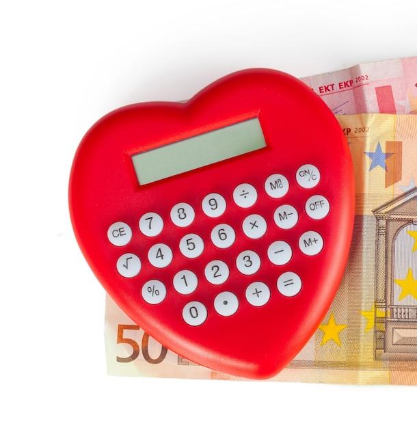 Rotes herz geformt taschenrechner mit euro-banknoten. Premium Fotos