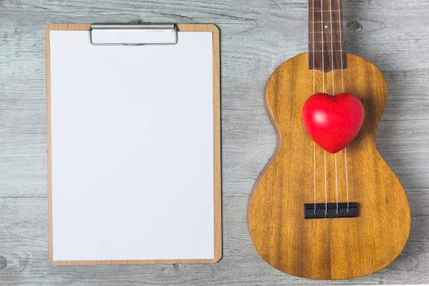 Rotes Herz; Gitarre und Weißbuch auf Klemmbrett über dem hölzernen ...