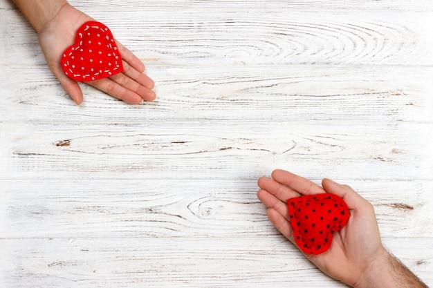 Rotes herz in den frauen- und mannhänden, auf hölzernem hintergrund Premium Fotos