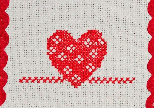 Rotes herz in kreuzstich auf leinwand gestickt Premium Fotos