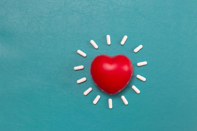 Rotes herz mit pillenhintergrund Kostenlose Fotos