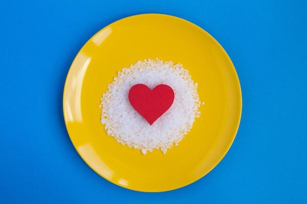 Rotes herz und salz in der gelben platte auf dem blauen hintergrund. draufsicht. kopierraum. Premium Fotos
