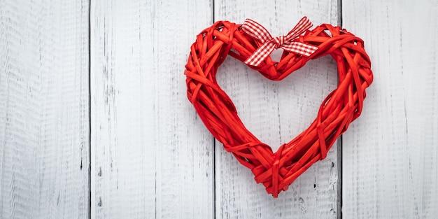 Rotes herz vom band auf weißem hölzernem hintergrund, schablone mit textraum. flach lag mit liebeskonzept, valentinskarte, modell. layoutdekoration. festlicher rahmen, kunstbanner. valentinstag - urlaub. Premium Fotos