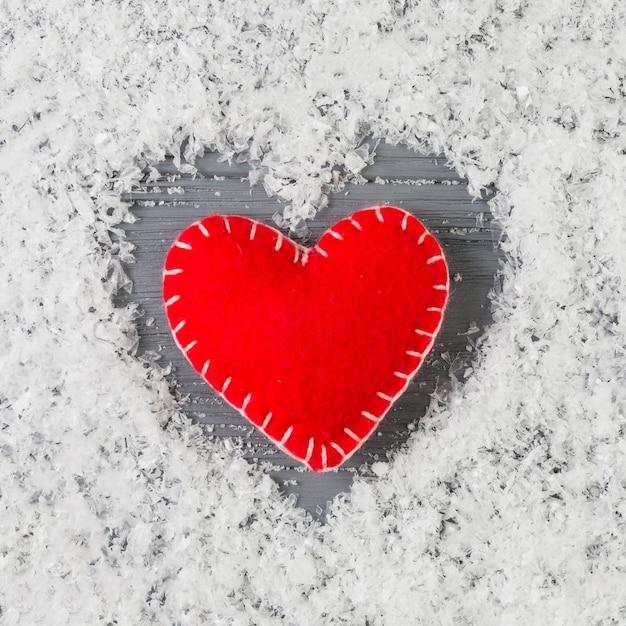 Rotes herz zwischen dekorativem schnee auf hölzernem schreibtisch Kostenlose Fotos