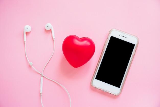 Rotes herz zwischen dem kopfhörer und smartphone auf rosa hintergrund Kostenlose Fotos