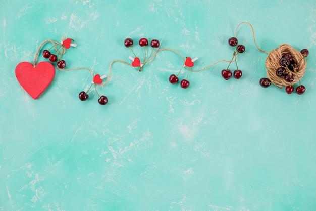 Rotes hölzernes herz und süße frische kirschen lokalisiert auf grünem hintergrund. liebe komposition. Premium Fotos