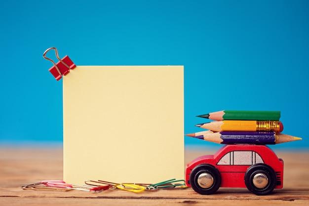 Rotes miniaturauto, das bunte bleistifte auf blau trägt Premium Fotos