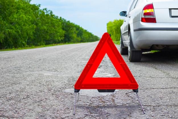 Rotes notauszeichen und defektes silbernes auto auf der straße Premium Fotos