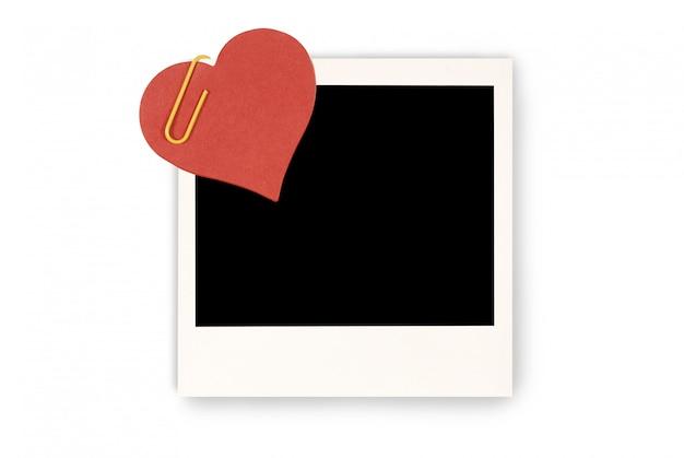 Rotes papierherz an einem leeren polaroidbilddruck befestigt Premium Fotos