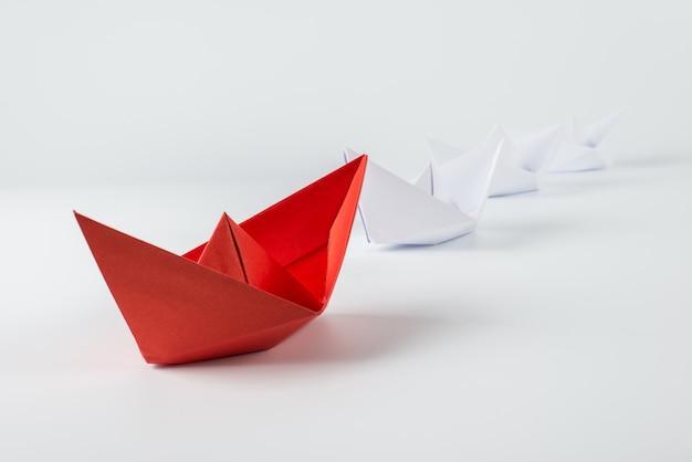 Rotes papierschiff, das unter weiß führt Premium Fotos