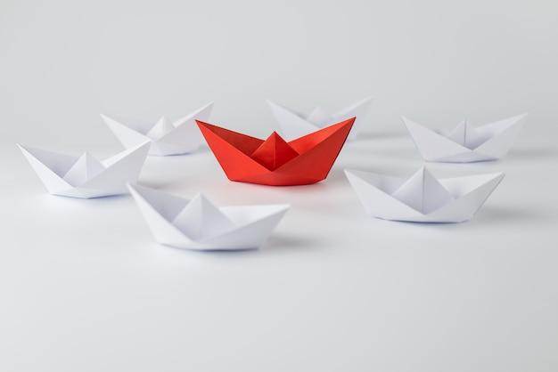 Rotes papierschiff, das unter weißem hintergrund führt Premium Fotos