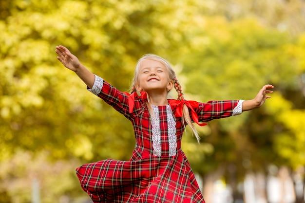Rotes plaidkleid des blonden erstklässlers des kleinen mädchens, das in der straße lächelt Premium Fotos