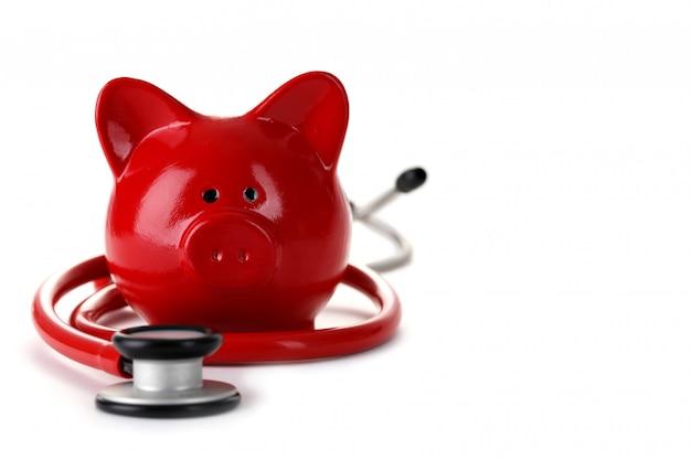 Rotes sparschwein mit dem stethoskop lokalisiert auf weiß Premium Fotos