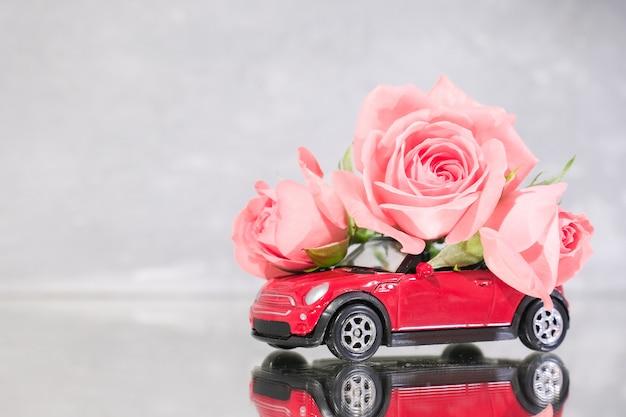 Rotes spielzeugauto, das blumenstrauß von rosarosenblumen liefert Premium Fotos