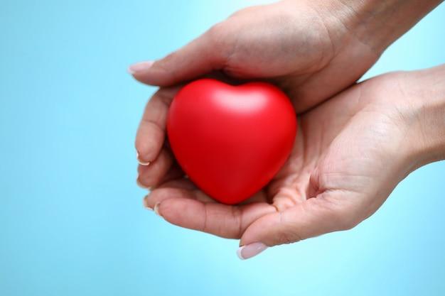 Rotes spielzeugherz des frauenhandgriffs in der hand gegen blaue hintergrundnahaufnahme. charity people-konzept Premium Fotos