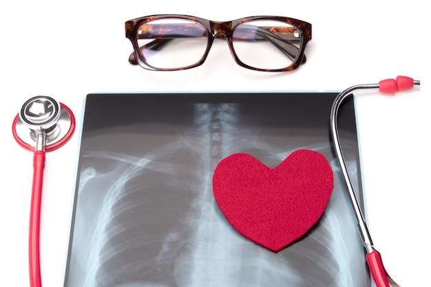 Rotes stethoskop des gesundheitswesens und der medizin und rotes herzsymbol auf röntgenstrahlfilm Premium Fotos