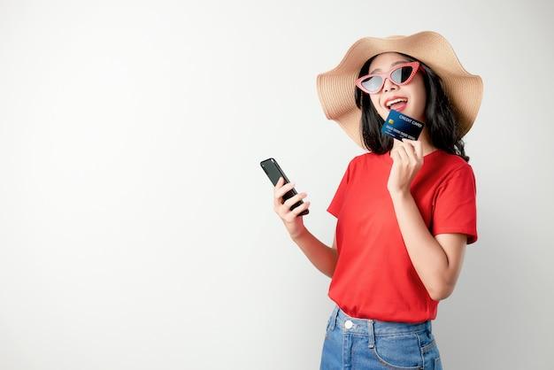 Rotes t-shirt der asiatin des lächelns glücklich, das den smartphone und kreditkarte online kaufen hält. Premium Fotos
