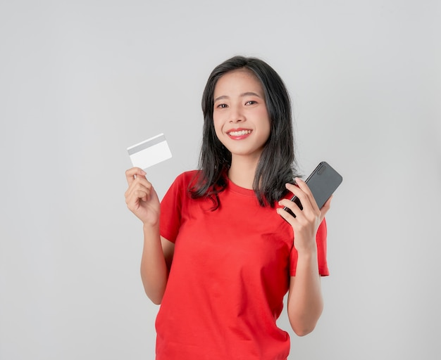 Rotes t-shirt der asiatin des lächelns glücklich, welches den smartphone und kreditkarte online kaufen auf grauem hintergrund hält. Premium Fotos