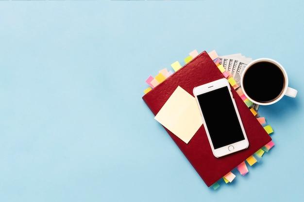Rotes tagebuch mit aufklebern auf den seiten, eine tasse mit schwarzem kaffee, hundert dollar, weißes telefon, blauer hintergrund. konzept eines erfolgreichen geschäfts, richtige planung, zeitmanagement. flache lage, draufsicht Premium Fotos