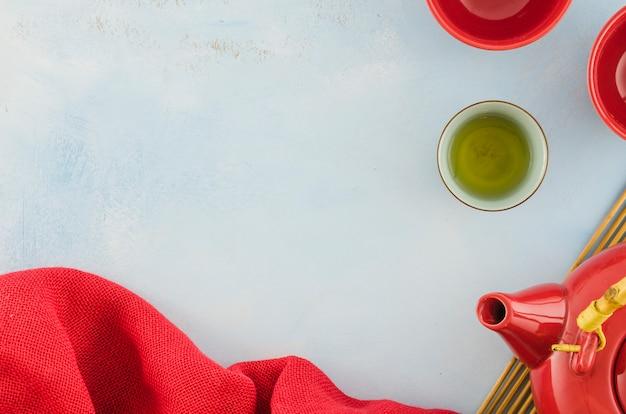 Rotes textil; teetassen und teekanne mit exemplar für das schreiben des textes auf weißen hintergrund Kostenlose Fotos