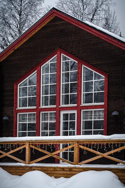 Rotes und braunes holzhaus mit großen fenstern im schnee in einem wald umgeben von bäumen Kostenlose Fotos