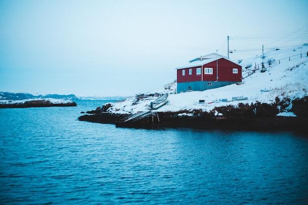 Rotes und graues haus nahe dem mit schnee bedeckten gewässer Kostenlose Fotos