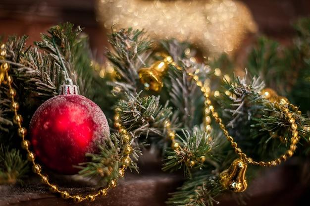 Rotes weihnachtsspielzeug unter den fichtenzweigen und den goldlichtern. Premium Fotos