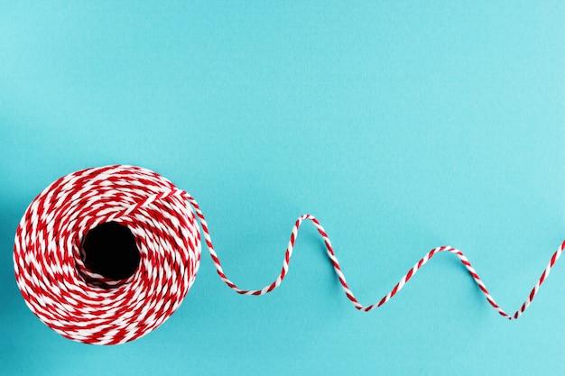 Rotes weißes verpackungsweihnachtsseil auf blauem hintergrund Premium Fotos