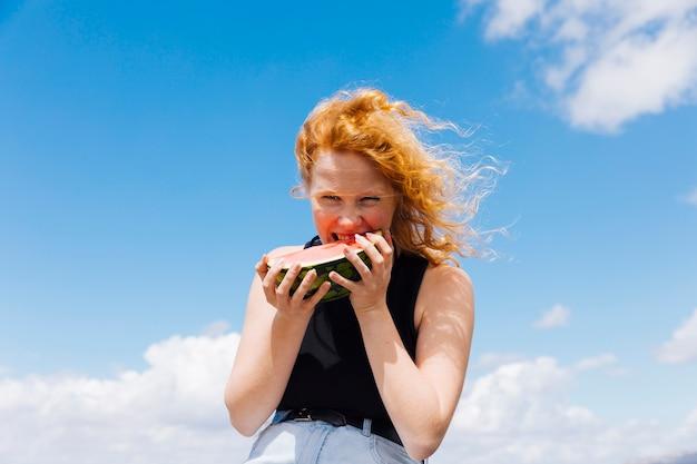 Rothaarige frau, die scheibe der wassermelone isst Kostenlose Fotos