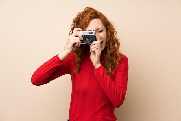 Rothaarige frau mit rollkragenpullover hält eine kamera Premium Fotos