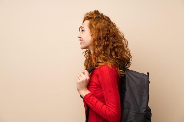 Rothaarige frau mit rollkragenpullover mit rucksack Premium Fotos