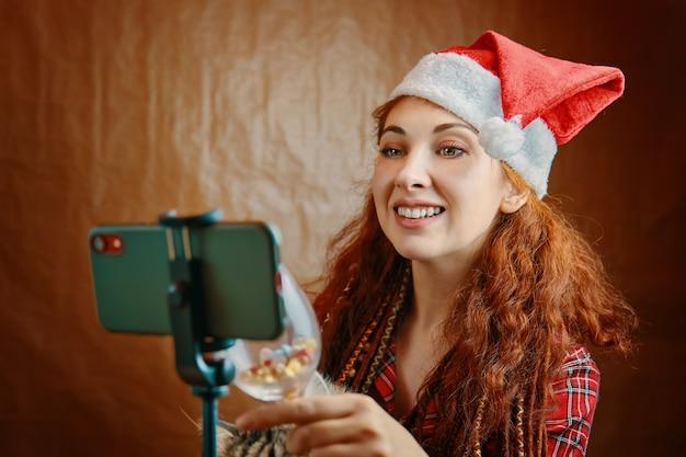 Rothaarige frau mit weihnachtsmütze und dreadlocks stößt glas auf smartphone an. virtuelles gespräch mit den eltern und video-chat. weihnachtsvideoanruf. Premium Fotos