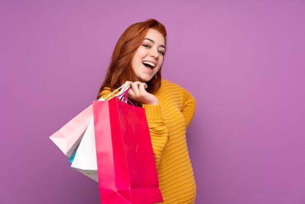 Rothaarige junge frau, die einkaufstaschen hält und lächelt Premium Fotos