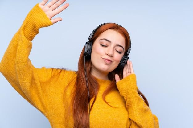 Rothaarige teenager-mädchen über blau hören musik und tanzen Premium Fotos