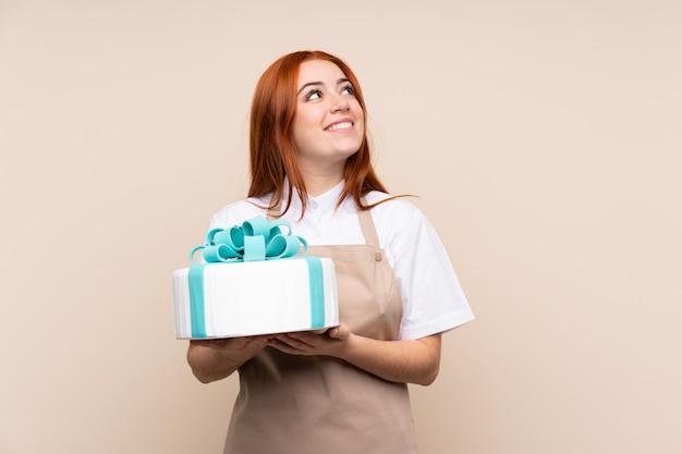 Rothaarige teenagerfrau mit einem großen kuchen, der beim lächeln nach oben schaut Premium Fotos
